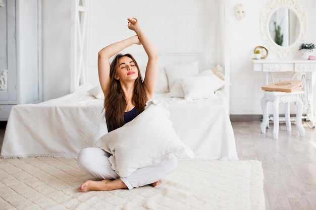 Woman relaxing in bed and holding pillow Free Photo