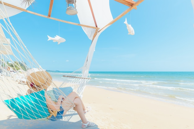 Woman relaxing in hammock on the beach Premium Photo