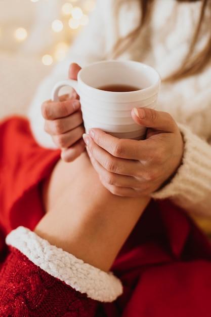 Donna che si distende a casa e che tiene una tazza di tè Foto Gratuite
