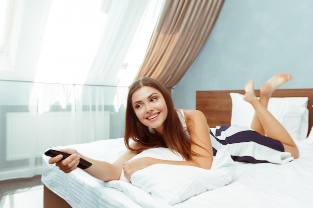 Woman relaxing in hotel room and looking tv Premium Photo
