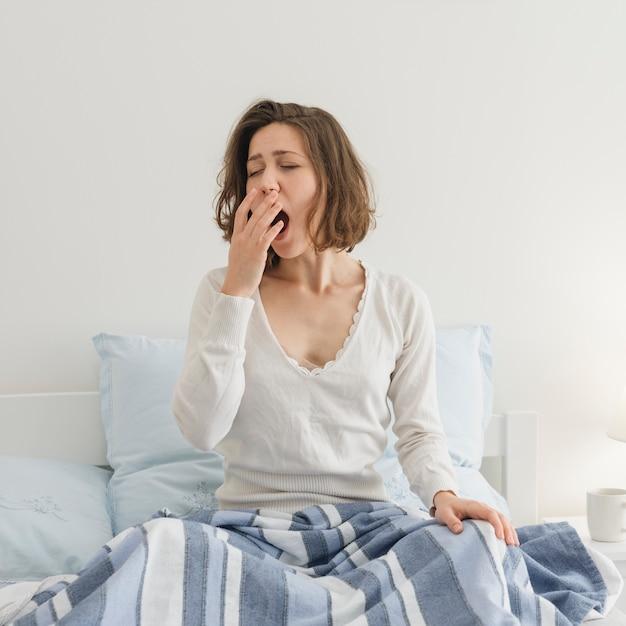 彼女のベッドでリラックスした女性 Premium写真