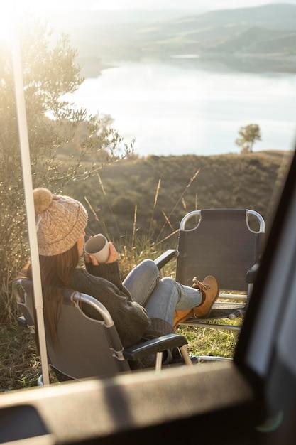 ロードトリップ中に車の横でリラックスする女性 無料写真