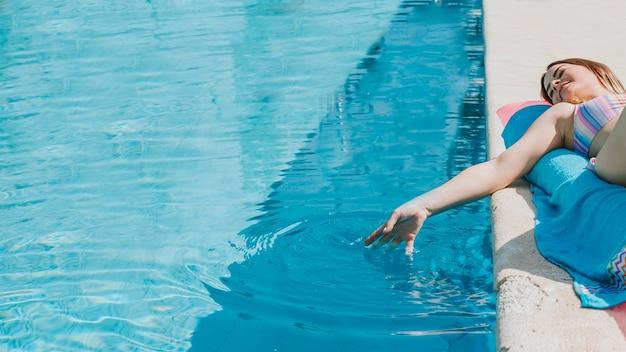 プールの隣でリラックスした女性 Premium写真