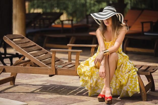 Woman relaxing outdoor on the lounger. lady in the hat. young female at summer. woman wearing yellow dress. Premium Photo