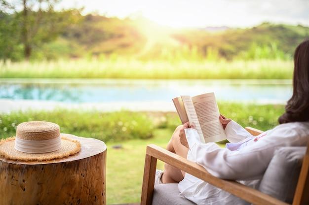 Женщина расслабляющий чтение книги в парке осенью Premium Фотографии