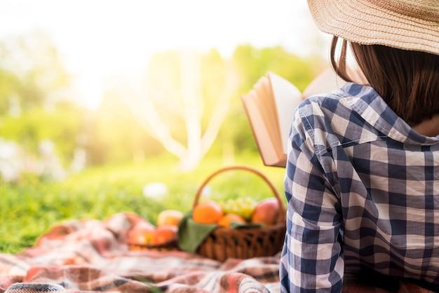 女性の公園でリラックスした読書本 無料写真