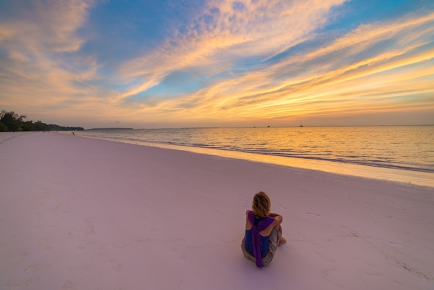 Woman relaxing on sand beach romantic sky at sunset, rear view, golden cloudscape, real people. indonesia, kei islands, moluccas maluku Premium Photo