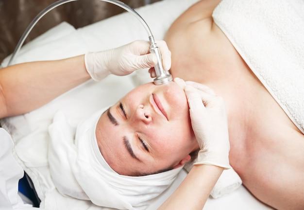 미용사는 그녀의 얼굴에 마사지 장치를 사용하는 동안 편안한 여자 프리미엄 사진