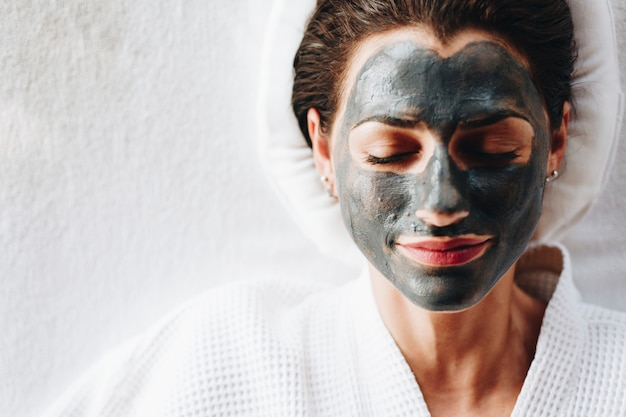 Woman relaxing with a charcoal facial mask Premium Photo