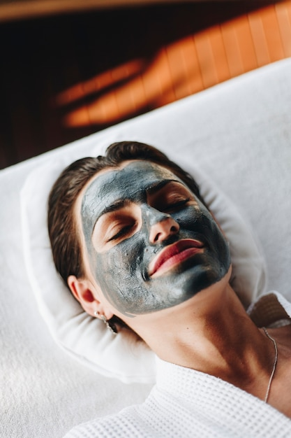 Woman relaxing with a facial mask at the spa Premium Photo