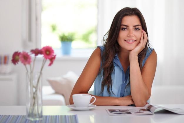 新聞とコーヒーでリラックスする女性 無料写真