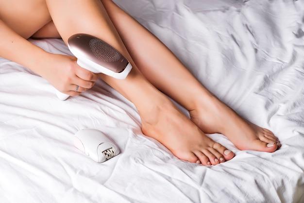 Женщина, удаляющая волосы со специальным оборудованием дома на кровати Premium Фотографии