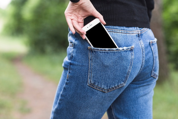 Woman removing smartphone from the blue jeans pocket Free Photo