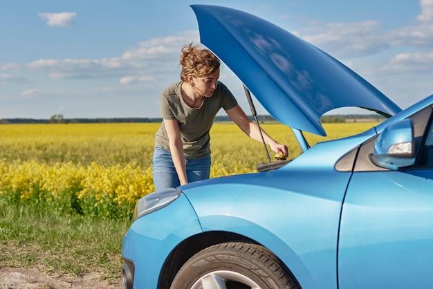 開いたボンネットで壊れた車を修理する女性 Premium写真