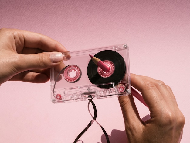 Woman repairing broken cassette tape with pink pencil Free Photo