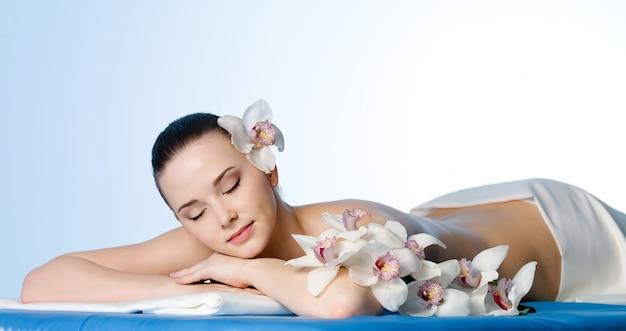 Donna che riposa nel salone di bellezza spa con fiori - spazio colorato Foto Gratuite
