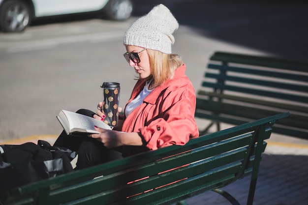 Woman resting on bench with book Free Photo