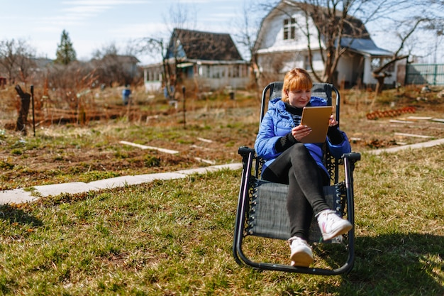 A woman resting in a chair with a tablet at her dacha Premium Photo