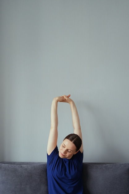 Woman resting on the couch in the living room and stretching her arms Free Photo