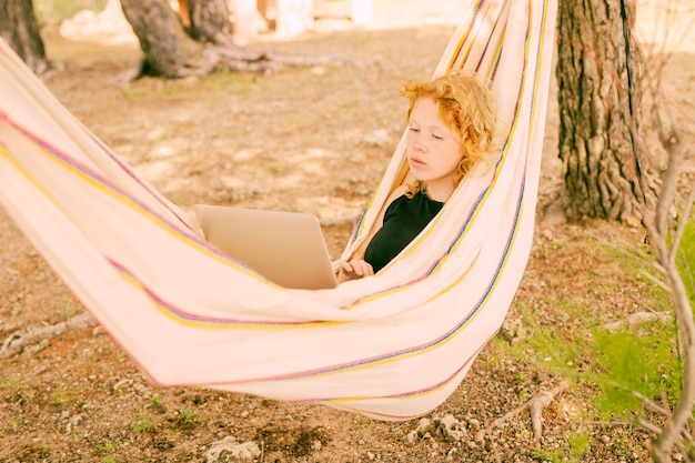 Woman resting in hammock with laptop Free Photo