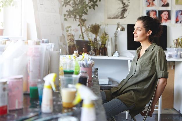 Женщина отдыхает в своей художественной студии Бесплатные Фотографии