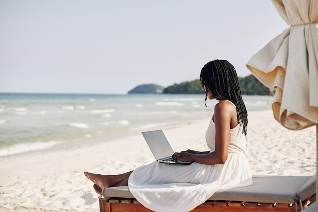 ノートパソコンとビーチで休んでいる女性 Premium写真