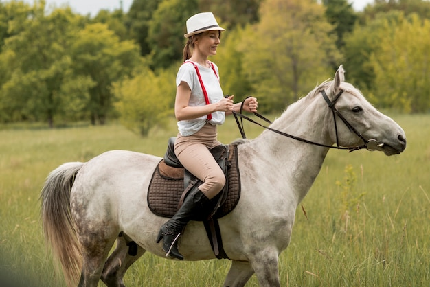 Woman ridding a horse in the countryside Free Photo