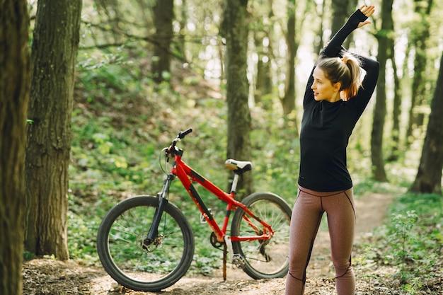 森の中のマウンテンバイクに乗る女性 無料写真