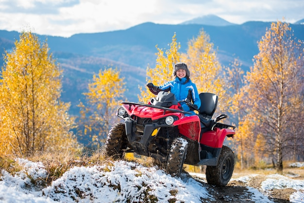 Woman riding a red quadbike on snow-covered hill at sunny day Premium Photo