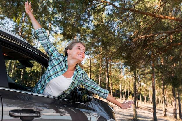 Женщина едет на машине и держит руки в воздухе Бесплатные Фотографии