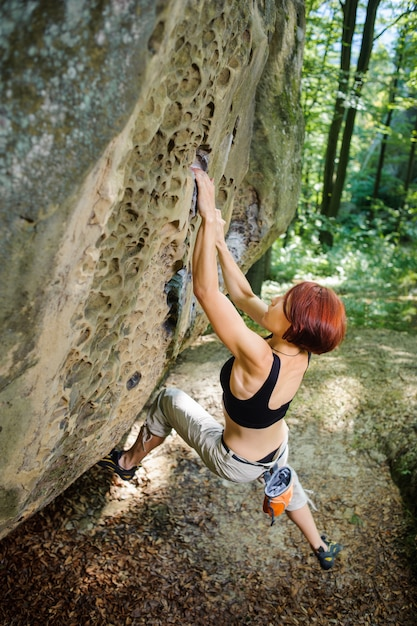 Woman rock-climber hanging on large boulder. outdoor Premium Photo