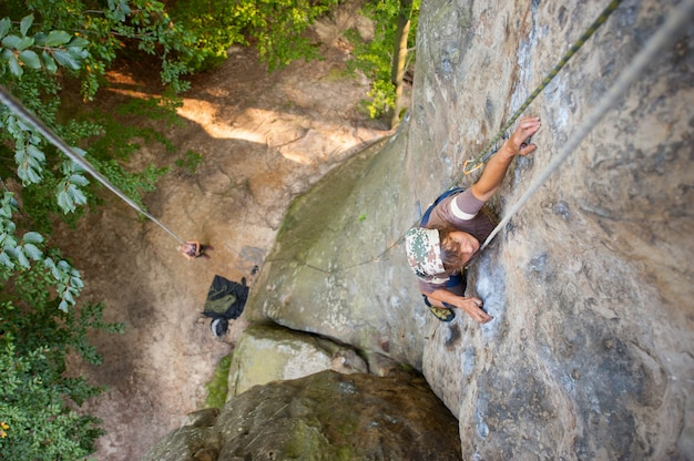 Woman rock climber is climbing with carbines and rope on a rocky wall Premium Photo