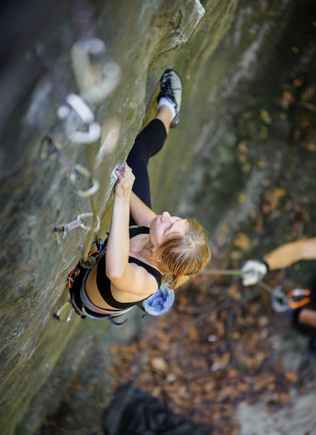 Woman rock climbing with carbines and rope Premium Photo