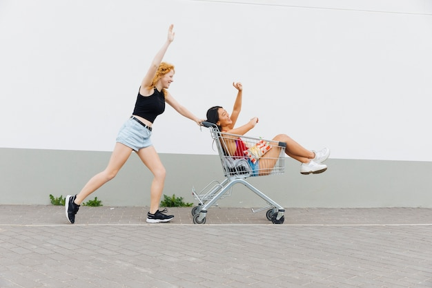 Woman rolling girlfriend with raised hands in shopping trolley Free Photo