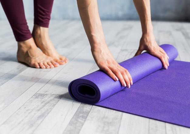 Woman rolling her yoga mat Free Photo