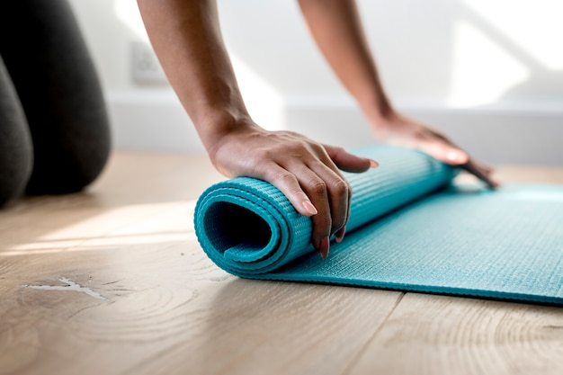 Woman rolling yoga mat Free Photo