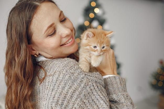 Donna in una stanza. persona con un maglione grigio. signora con piccolo gattino. Foto Gratuite