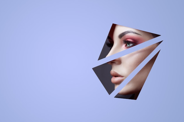Woman in a round hole circle in purple wall, beauty makeup cosmetics nature fashion, copy space advertising. professional makeup perfect skin and shiny lipstick. Premium Photo