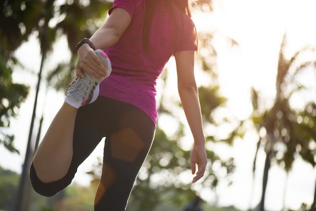 Woman runner stretching legs before run.outdoor exercise activities. Premium Photo