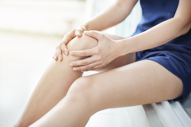 Woman runner suffering from knee pain sit on the floor Premium Photo