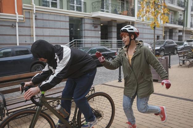 泥棒が自転車を盗んで犯人を捕まえようとして走っている女性 Premium写真