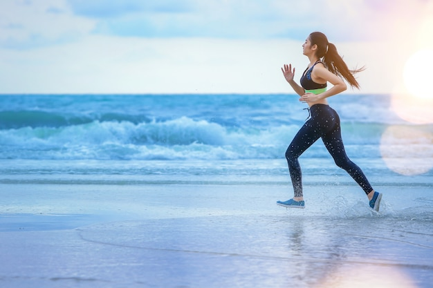 Woman running at the beach with sunset. Premium Photo