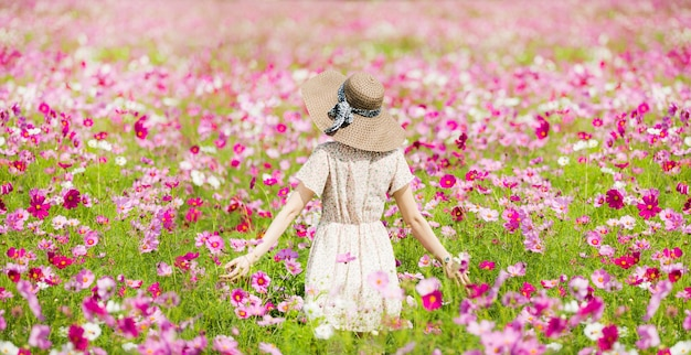 Woman running in the garden flowers cosmos flowers to touch her. Premium Photo