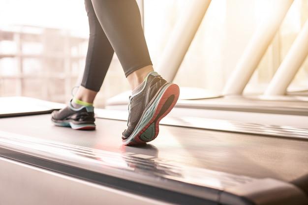 Donna che corre in una palestra su un concetto di tapis roulant per l'esercizio, la forma fisica e lo stile di vita sano Foto Gratuite