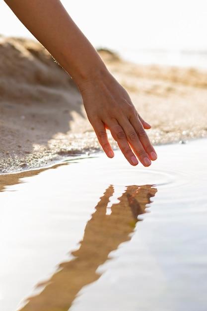 ビーチで水を介して彼女の手を走っている女性 無料写真