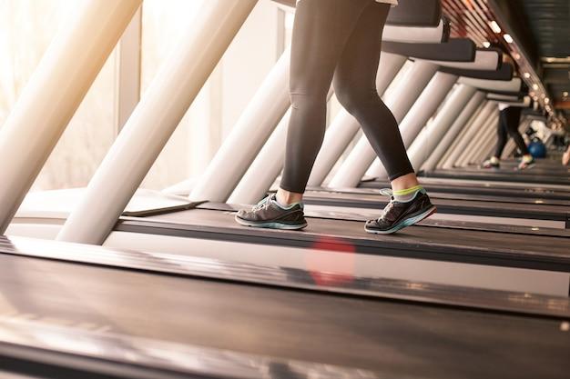 Женщина работает в тренажерном зале на беговой дорожке с концепцией упражнений, фитнеса и здорового образа жизни Бесплатные Фотографии