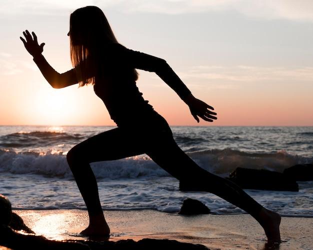 Женщина работает на пляже на закате Бесплатные Фотографии
