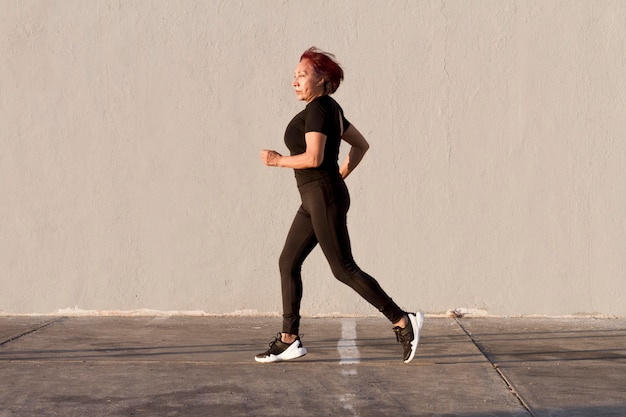 Woman running outdoors side view shot Free Photo