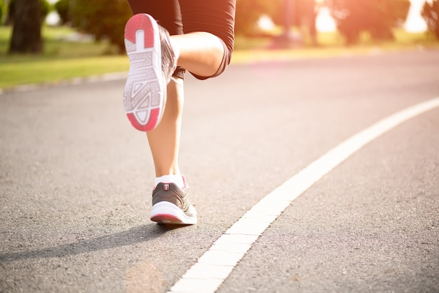 Woman running towards on the road side. step, run and outdoor exercise concept. Premium Photo