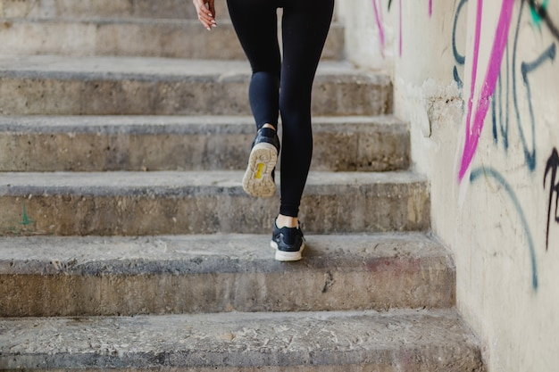 Woman running up stairs outside Free Photo